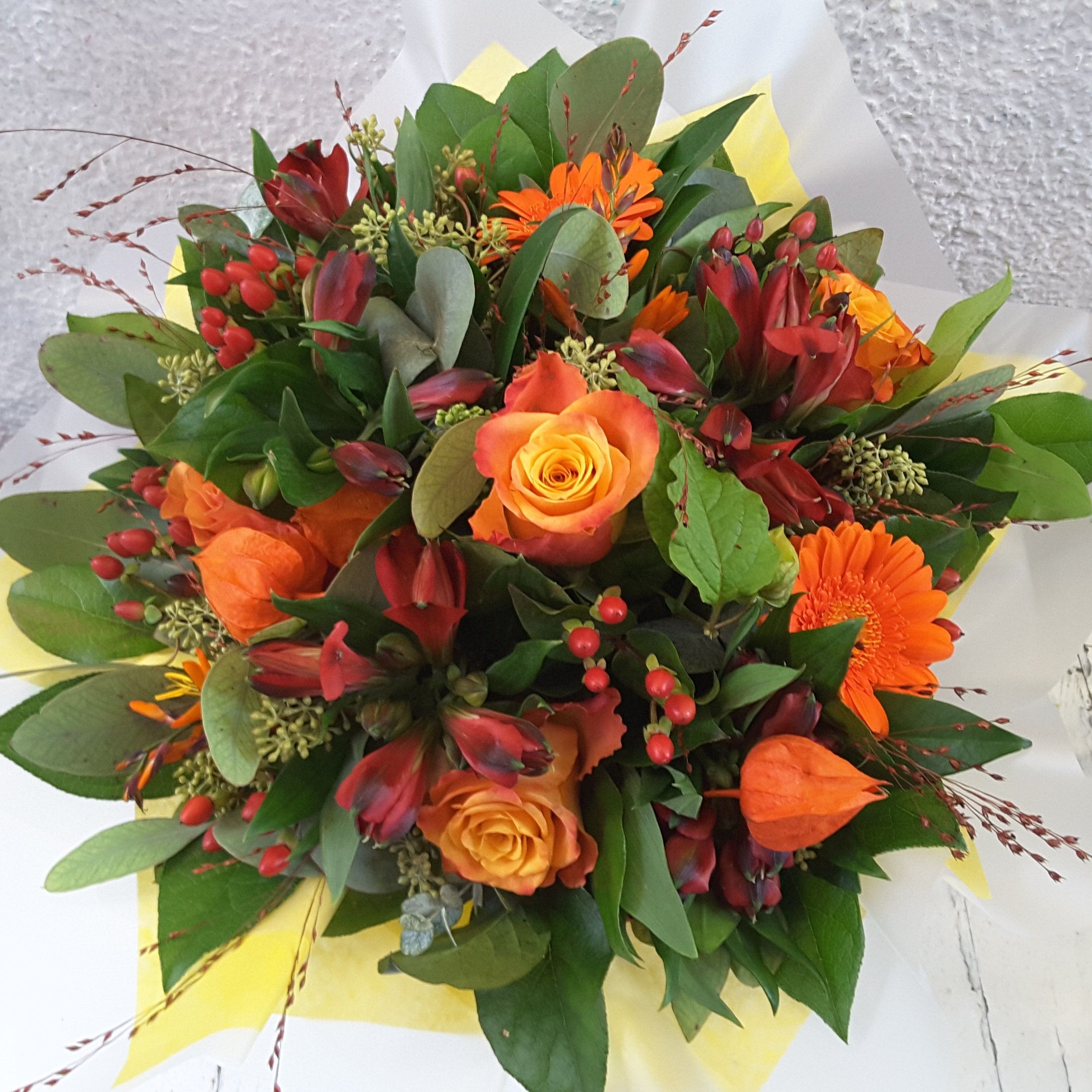 A Bright Handtied Bouquet Of Orange Flowers Seasonal Berries And