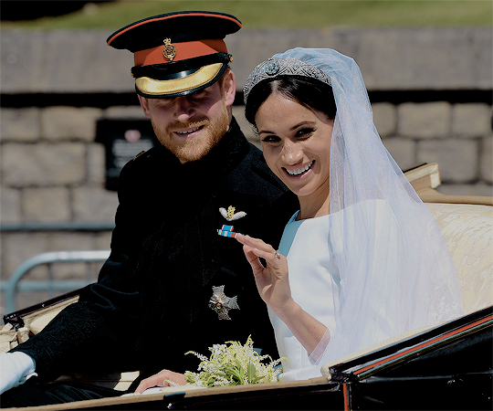 The newly married royal couple, the Duke and Duchess of Sussex, wave to the crowds during their ...