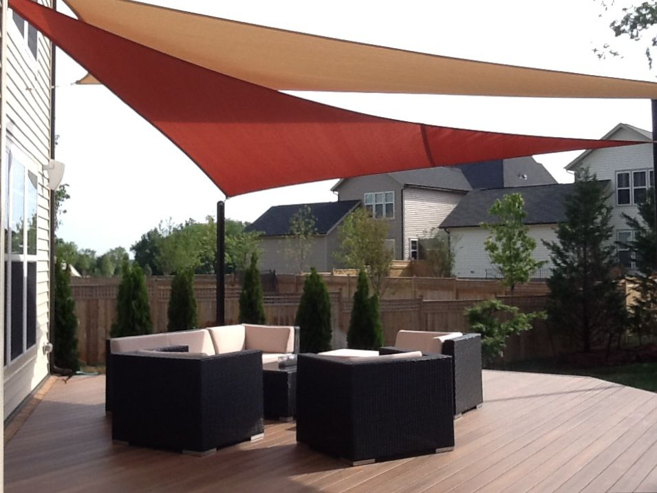 Triangle rust and rectangle khaki shade sails for color and interest in a cookie cutter rear yard.