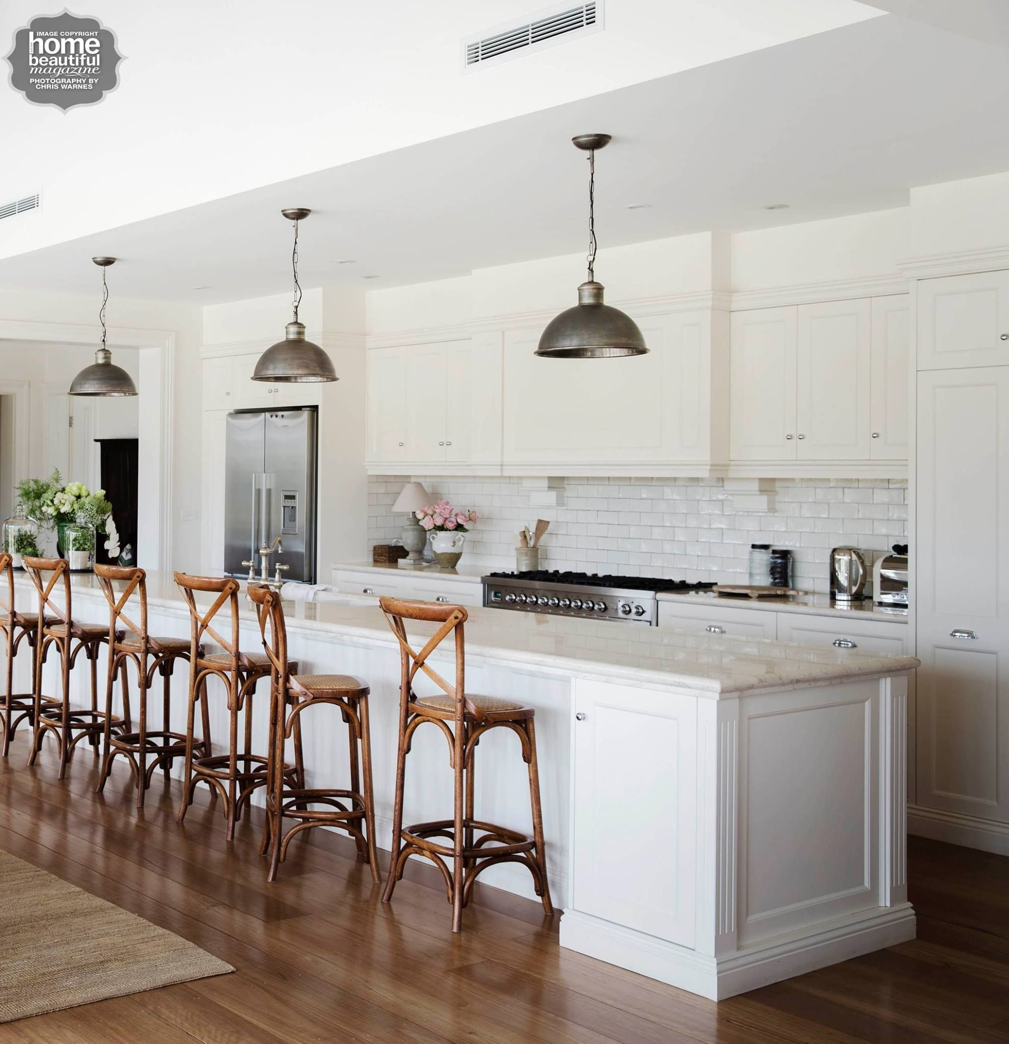 Tile texture, industrial lighting and appliances with wood chairs ...