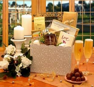 """Romance is in the air with this classic and elegant wedding gift box. Gorgeous roses are gathered together with a stylish yet delicious coordinated look that is unforgettable. The Happily Ever After Wedding Gift Box includes: Los Olivos garlic & Cheddar wine biscuits, Focaccia parmesan crusted crackers, Chamberry raspberry chocolate truffles, Frosted votive candles, chocolate body frosting, frosting paintbrush, 2.2 oz Angelinas bite-size cookies, 5x7 gold picture frame, """"Love"""" A book of ins"""