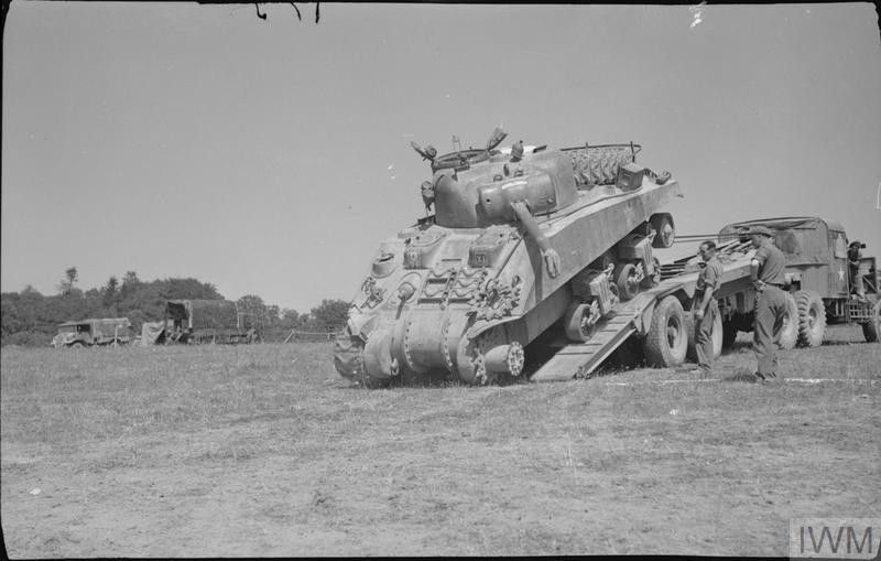 A disabled Sherman tank being unloaded from the back of a Scammell tank transporter, 13 August 1944.