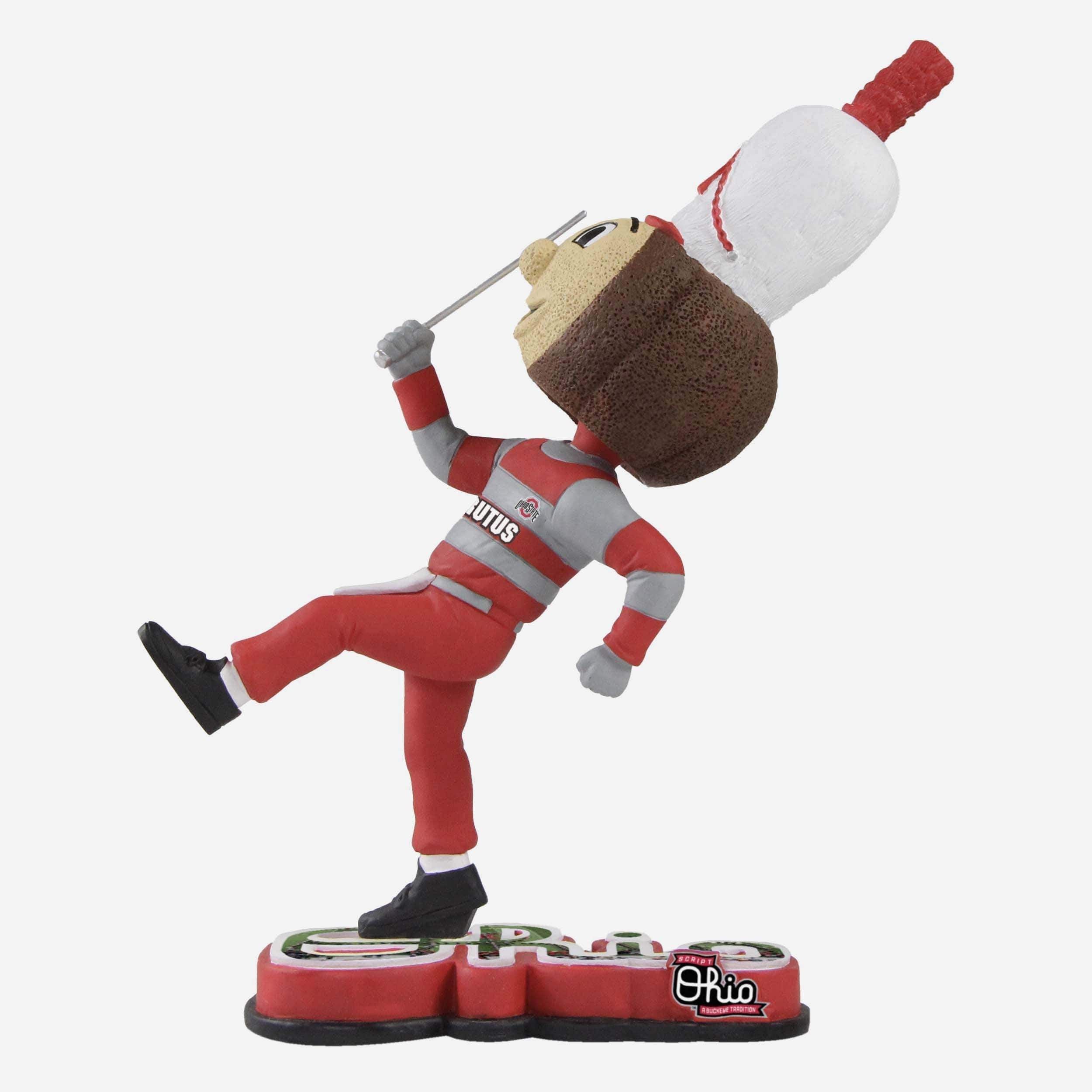 *SEP* *SEP* Get ready to have your own personal halftime show any time you want. With this Brutus Buckeye Drum Major Ohio State Buckeyes Halftime Heroes Mascot Bobblehead, you can proudly march to the beat of your own drum. Features Portrays Brutus wearing band hat posing with a baton, ready to entertain a crowd Raised base in shape of team name, so your mascot can rep your school Front team logo display so everyone knows who you're rooting for Handcrafted Hand painted Measurements Height: Appro