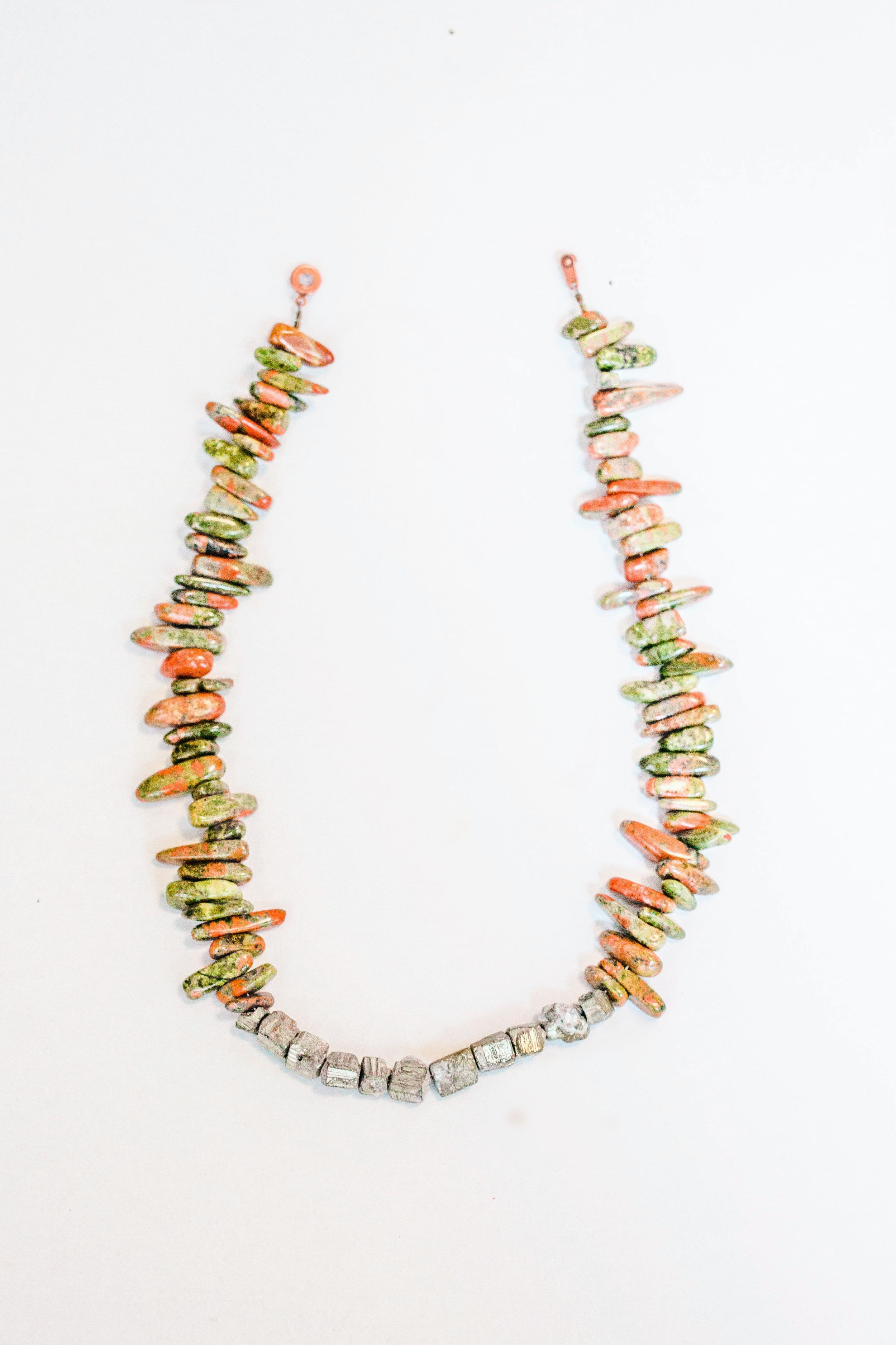 The Azalea Road Necklace: this unakite tusk stone necklace features 11 raw unpolished pyrite beads in the center and has an antique brass button clasp.