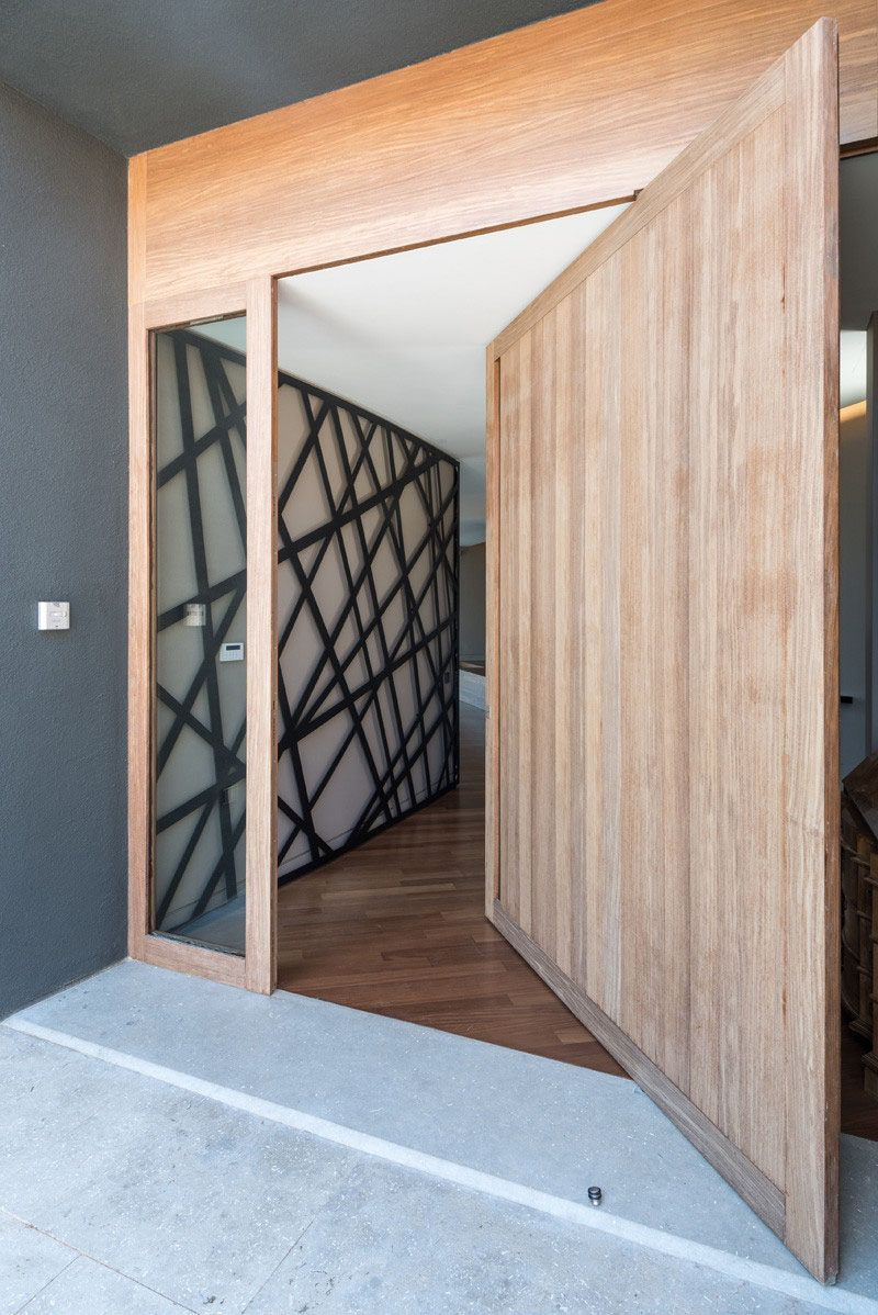 Modern Wood Door. A Large Light Wood Pivoting Door Greets People At The  Front Of