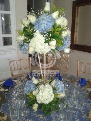 El centro de mesa es un candelabro en hierro can base y cabecera floral