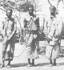Three people in chains, probably somewhere in East-Africa. By 1900, slaves comprised up to one-third of Ethiopia's population. Emperor Haile Selassie officially abolished slavery in 1942.