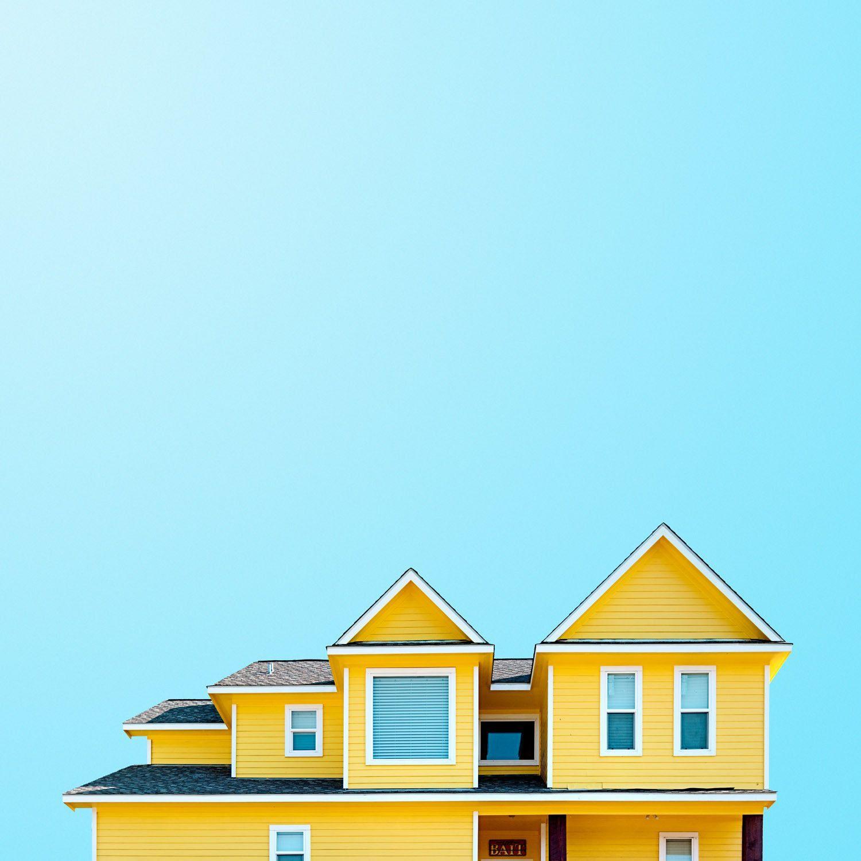 A modern yellow beach house against a bright blue sky.