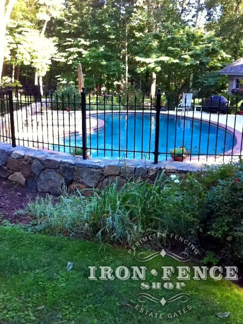 Wrought Iron Fence Installed On A Stone Wall Around A Pool And