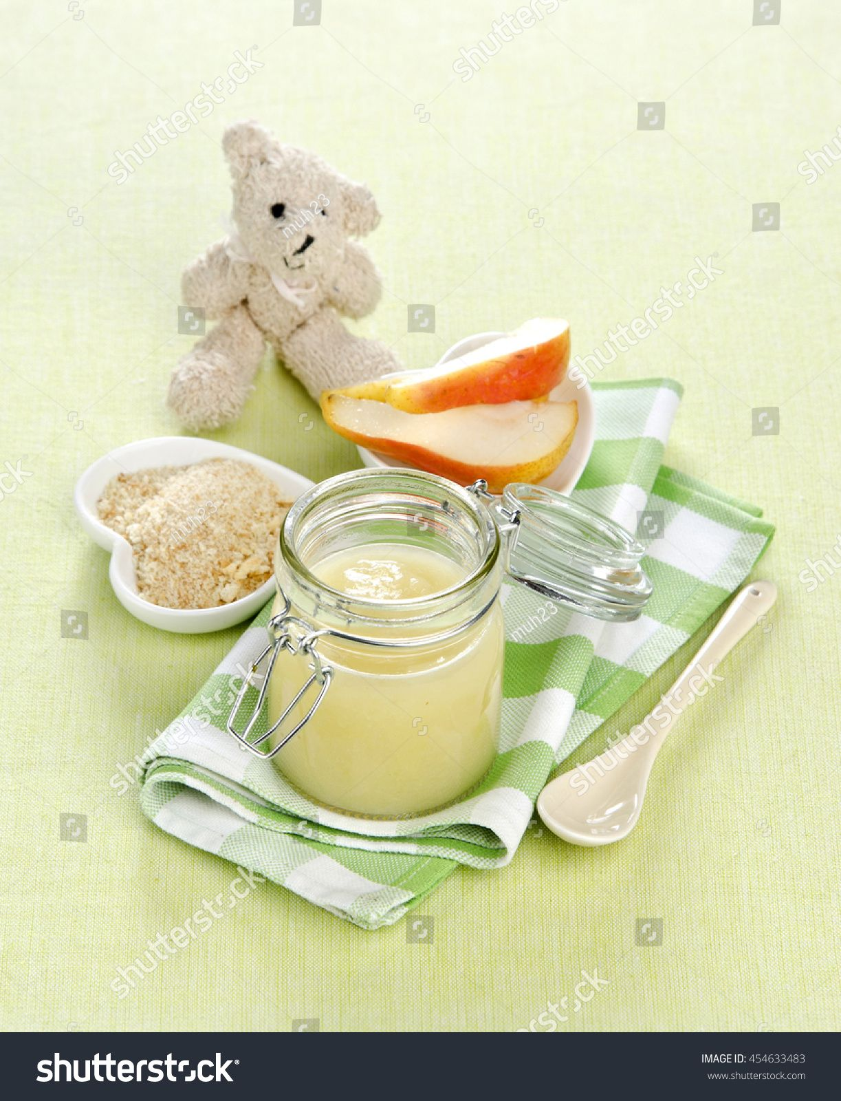 baby food puree of pear fruit in a bank with a toy bear