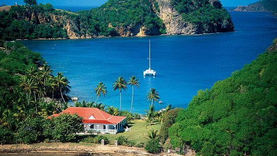 Guadeloupe. One of the 2 prettiest, most lush islands in the Caribbean. French. Beautiful beaches where you can sunbathe and maybe see a local carrying home a small shark for dinner, good snorkeling, good food all with a background of steel drum bands. Helpful if you can speak French.
