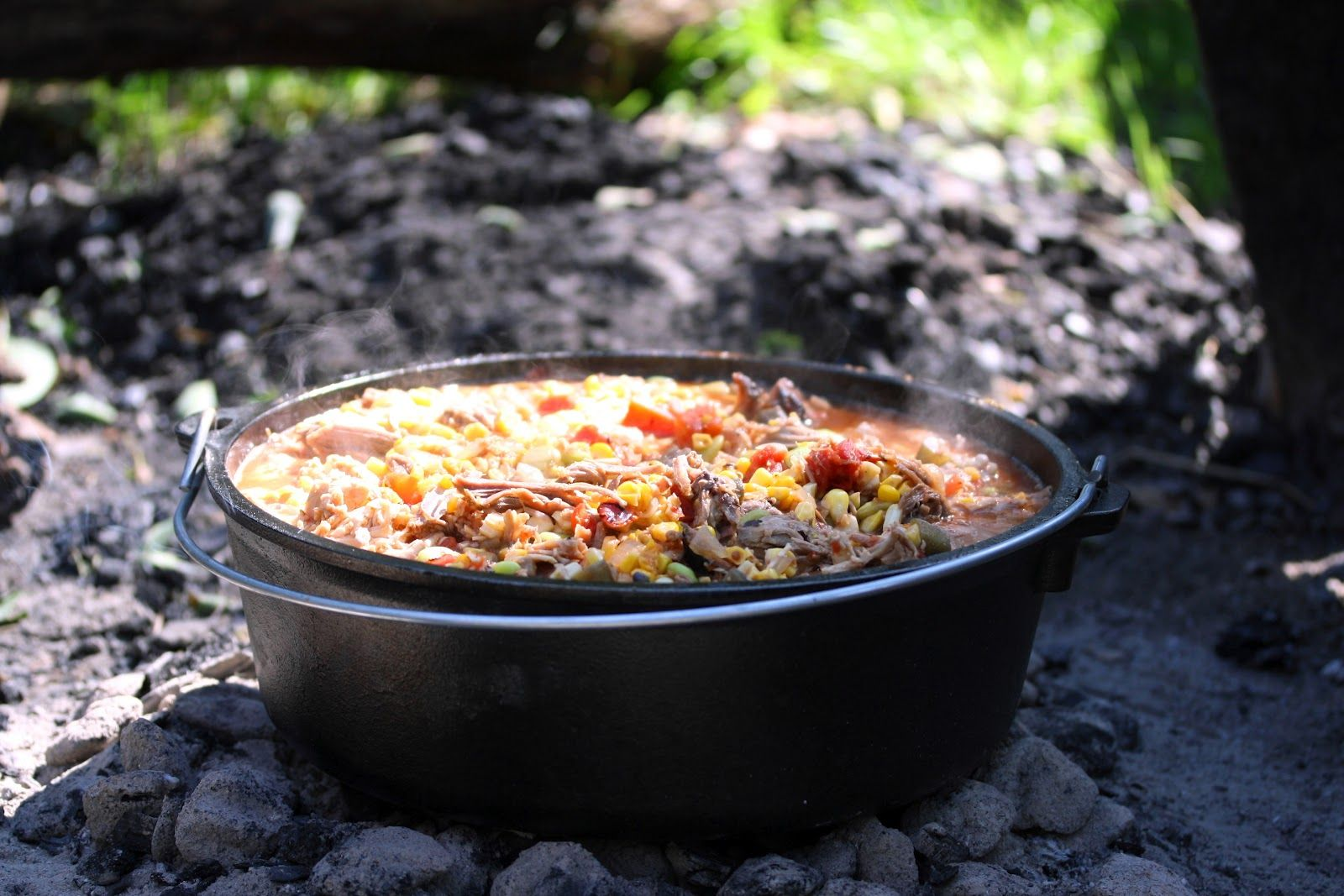 Brunswick Stew - tomato based stew with lima beans, okra, corn & vegetables with a variety of smoked meats cooked over hot coals in a Lodge Dutch Oven.