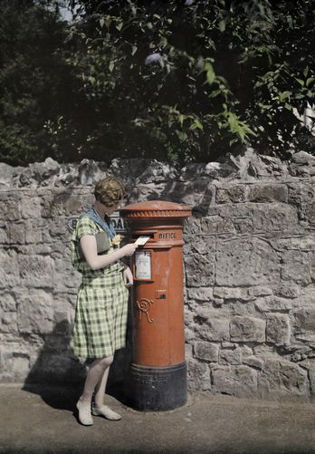 Clifton Adams. 1920s. A young woman mails a letter in a red pillar box. Ventnor, Isle of Wight, England.
