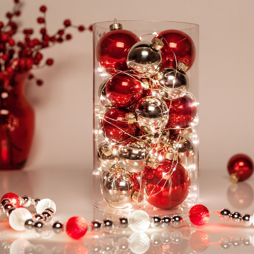 create a glowing christmas table centerpiece using ornaments and fairy string lights more