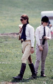 Jackie kennedy lleva botas, pantalones con sólo el paseo derecho agregado por sus gafas de sol de gran tamaño y el arco negro sobre la camisa blanca.