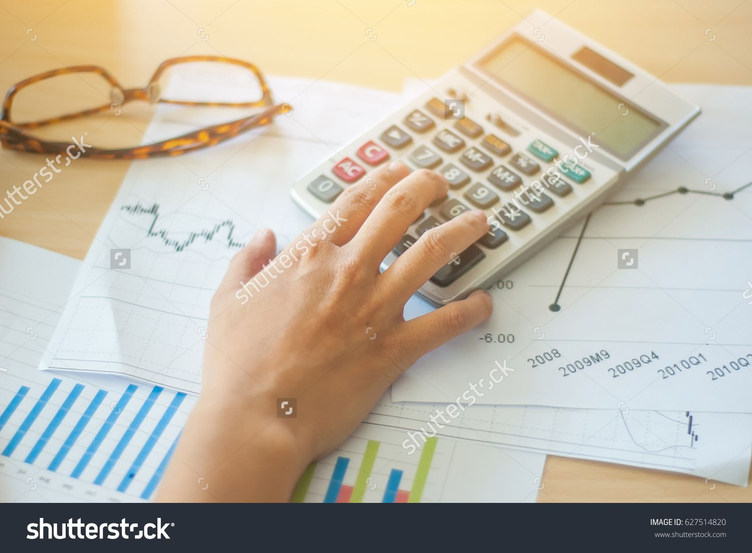 Calculator with woman hand doing finance and calculate on desk about cost at home office.