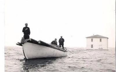 Moving a house vie the Atlantic Ocean using empty oil barrels and a boat, Newfoundland, 1960.