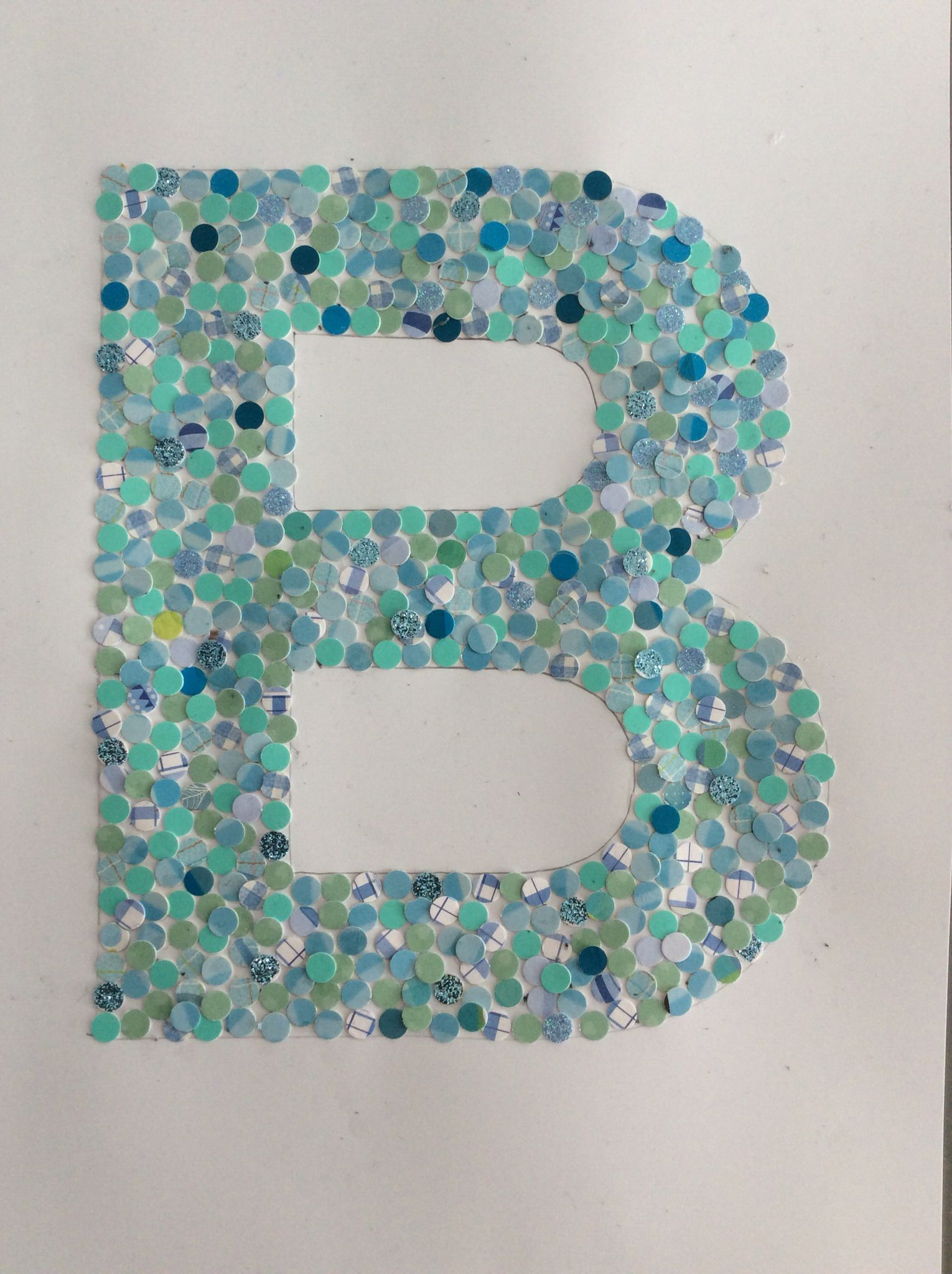 Confetti letter! When my son was born, we received a lot of postcards. I made confetti out of it, and glued them into the silhouet of the first letter of his name Beau. Nice to put in a photophrame for his room.