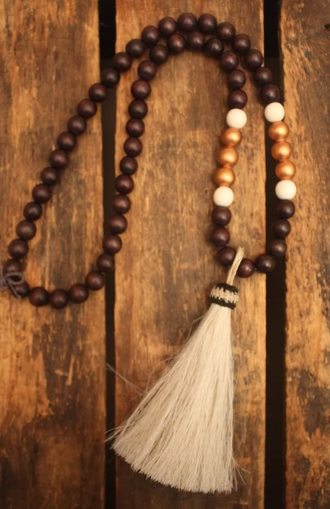 Large pendant necklace with white horsehair tassel.