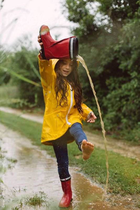 Girl In Yellow Raincoat Pouring Water From Her Boot And