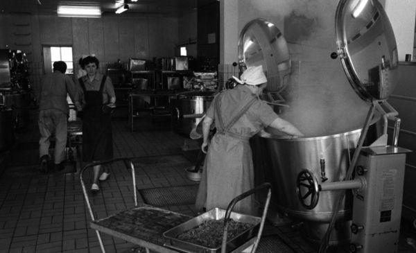 DigitaltMuseum - Henning Kjellgrens bageri, 18 april 1966 I förgrunden syns en kvinna röra om i en jättegryta inne i köket på Henning Kjellgrens bageri. Hon har arbetsuniform på: klänning med förkläde, samt huckle på huvudet. Till vänster kommer en annan kvinna gående iklädd arbetsklänning, förkläde, hatt på huvudet samt träskor. I bakgrunden syns en man med ryggen mot kameran och iklädd arbetsjacka och arbetsbyxor samt med hatt på huvudet köra ut en vagn. I förgrunden syns även en vagn med…