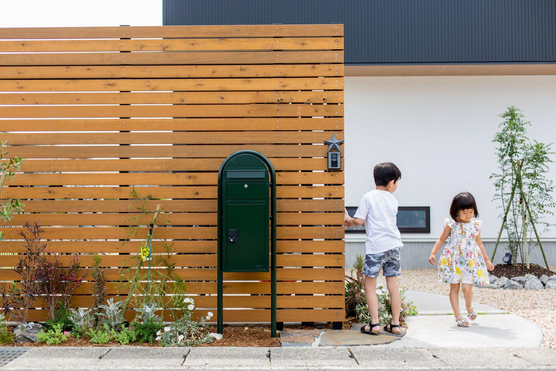 玄関アプローチの板塀裏に設えた自転車置き場 植栽やポストとの