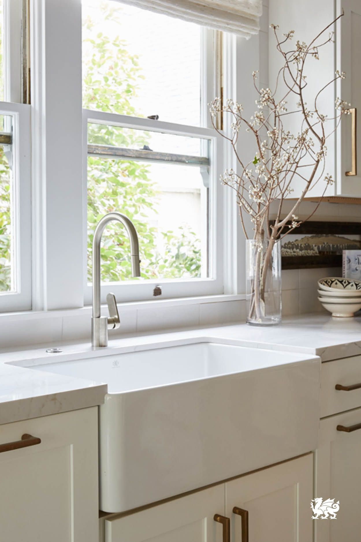 A beautiful white farmhouse sink takes center stage in this ...