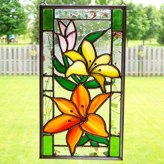 "Flowers feed the soul.    Streaky orange, yellow and pink stained glass shape the lovely flower petals. Leaves and stems are wispy green. The clear background glass has raised dots that look like rain. A border of green and red glass shards and glass threads float in clear. Spring green finishes the four corners.    Wire and solder form stamen detail in the flowers.    It measures 10 3\/8"" tall , 5 5\/8"" wide.    The glass in this piece was carefully cut, wrapped in copper foil and…"