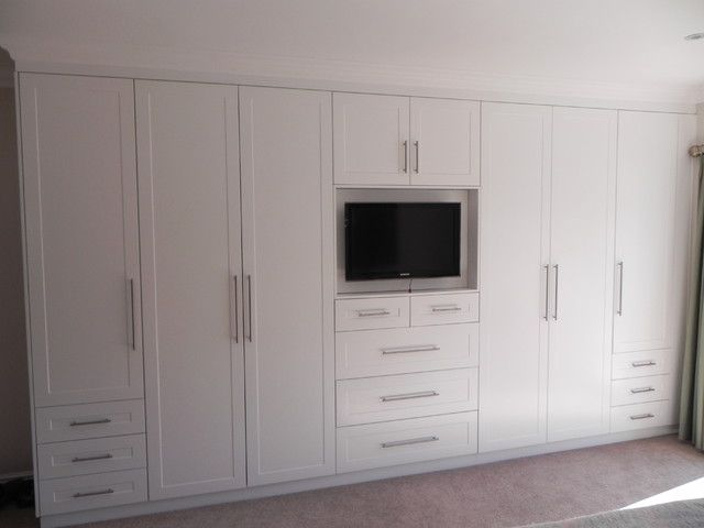 white bedroom cupboards with stylish television built in