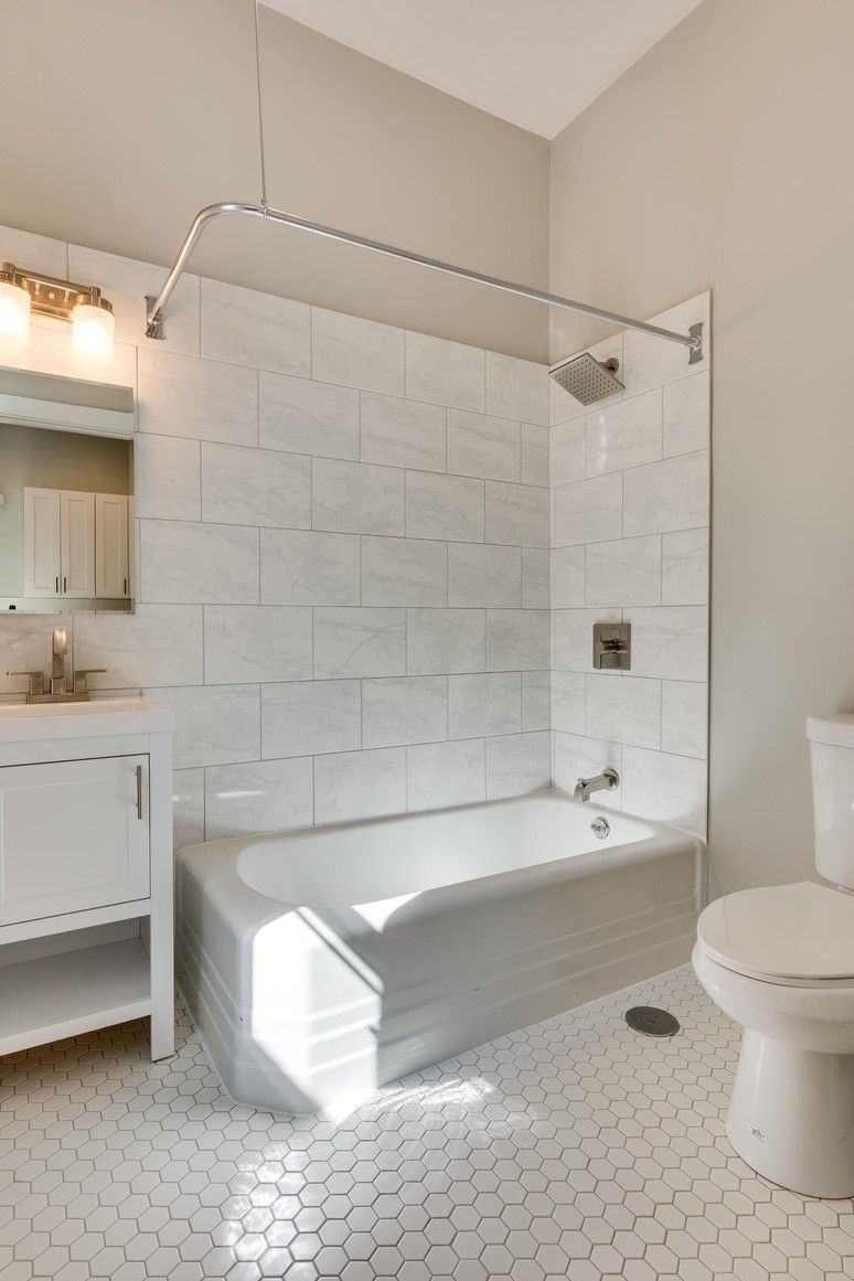 Modern Bathroom With White Hexagon Tile Rainfall Shower Head Pendant Lighting Vaulted Ceilings Wood Vanity And Marble Wall Domu Chicago