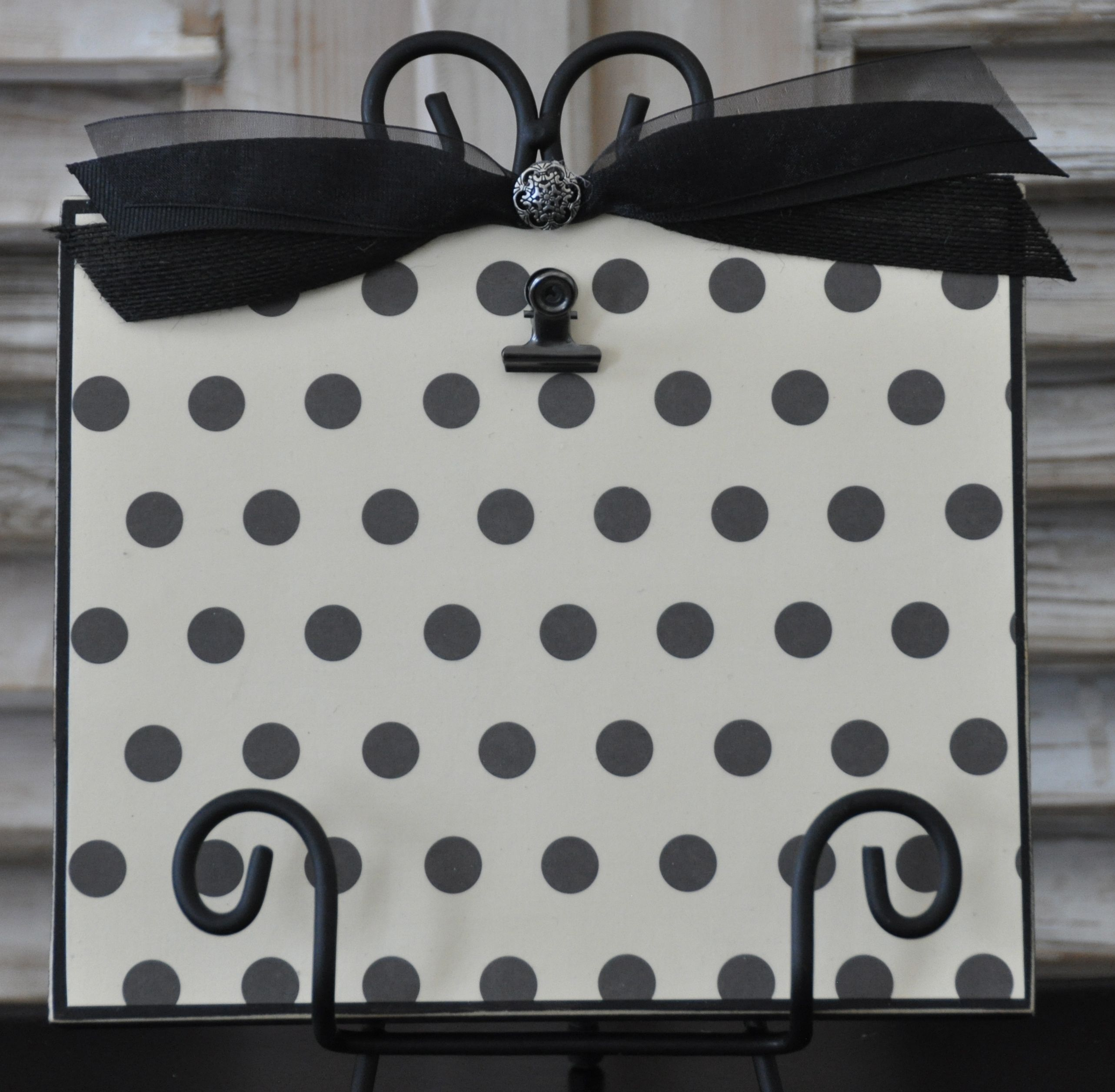 Black distressed frame with iron stand.  Embellished with black and creme polka dots and black bow.  Will hold up to a 5x7 photo.