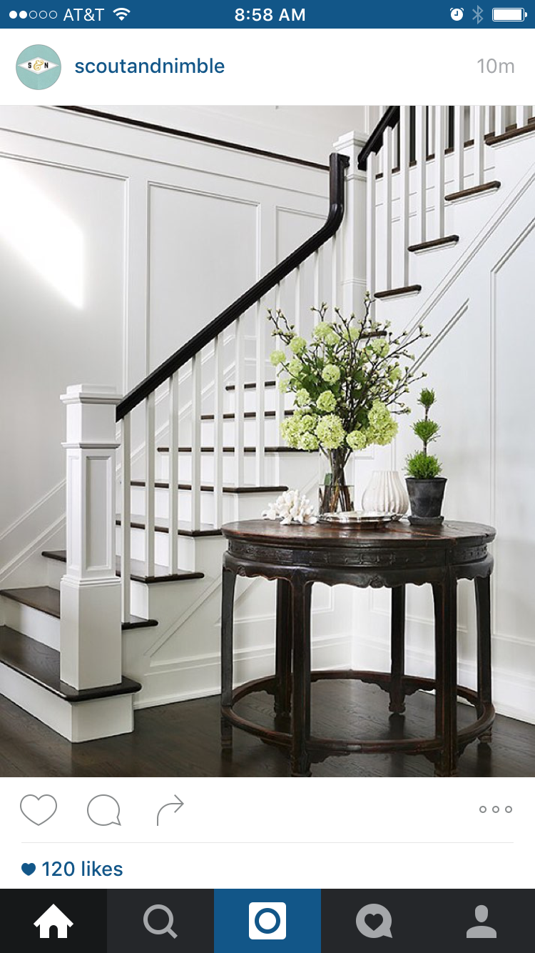 Chic foyer opens to a staircase fitted with white spindles and a black  railing. A wainscoted staircase wall is lined with a round antique foyer  table.