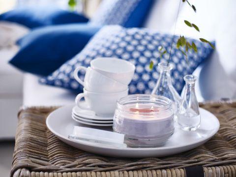 Hvidt fad med et duftlys, en stabel kopper og 2 glasvaser med blå og hvide puder i baggrunden