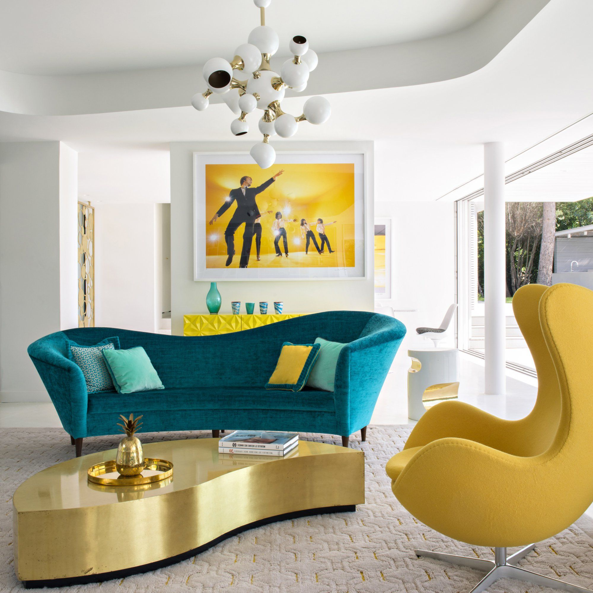 un salon aux couleurs pop avec un sofa bleu canard et un fauteuil egg jaune une table basse. Black Bedroom Furniture Sets. Home Design Ideas