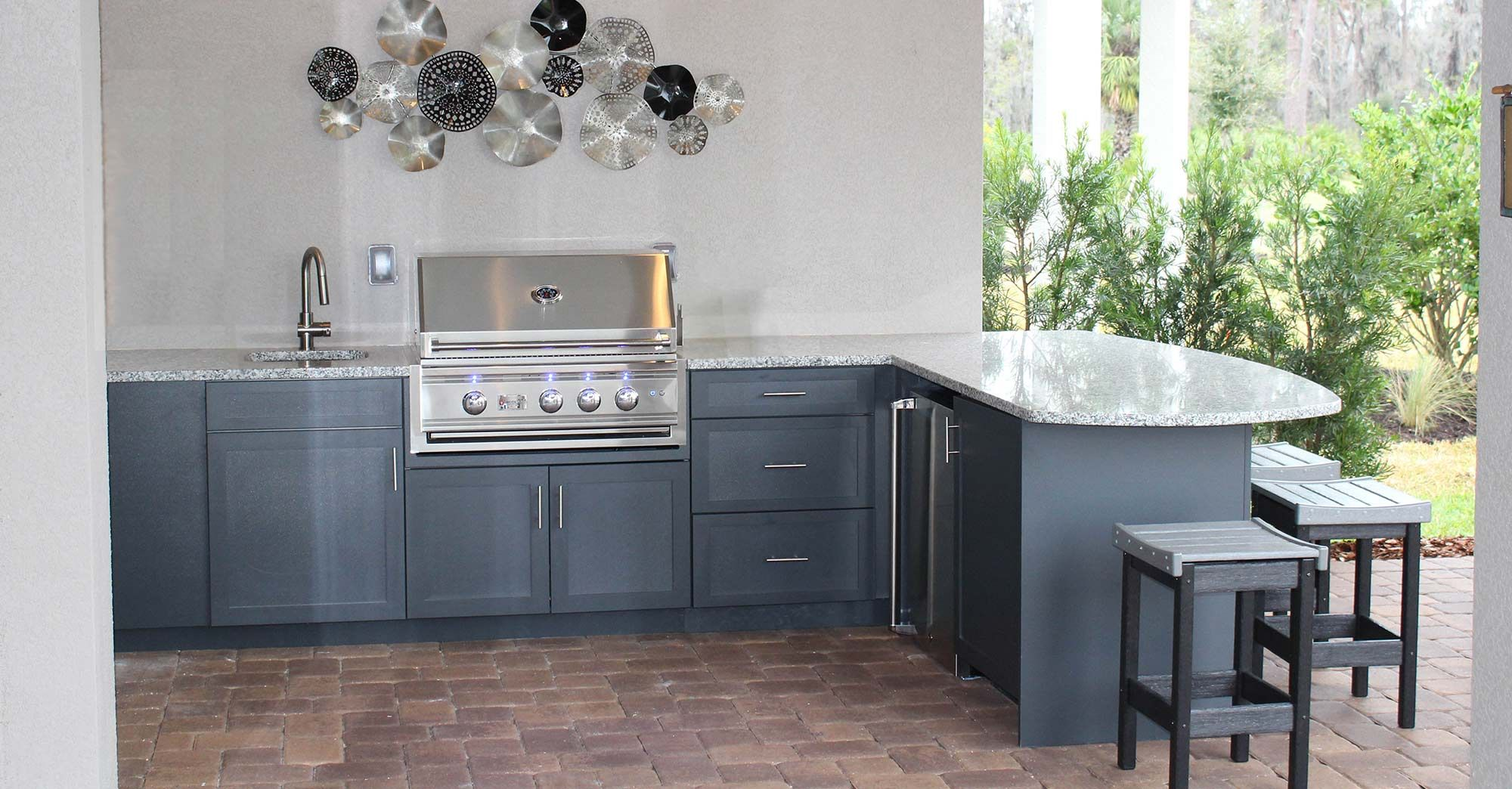 This outdoor kitchen features our custom weatherproof ...
