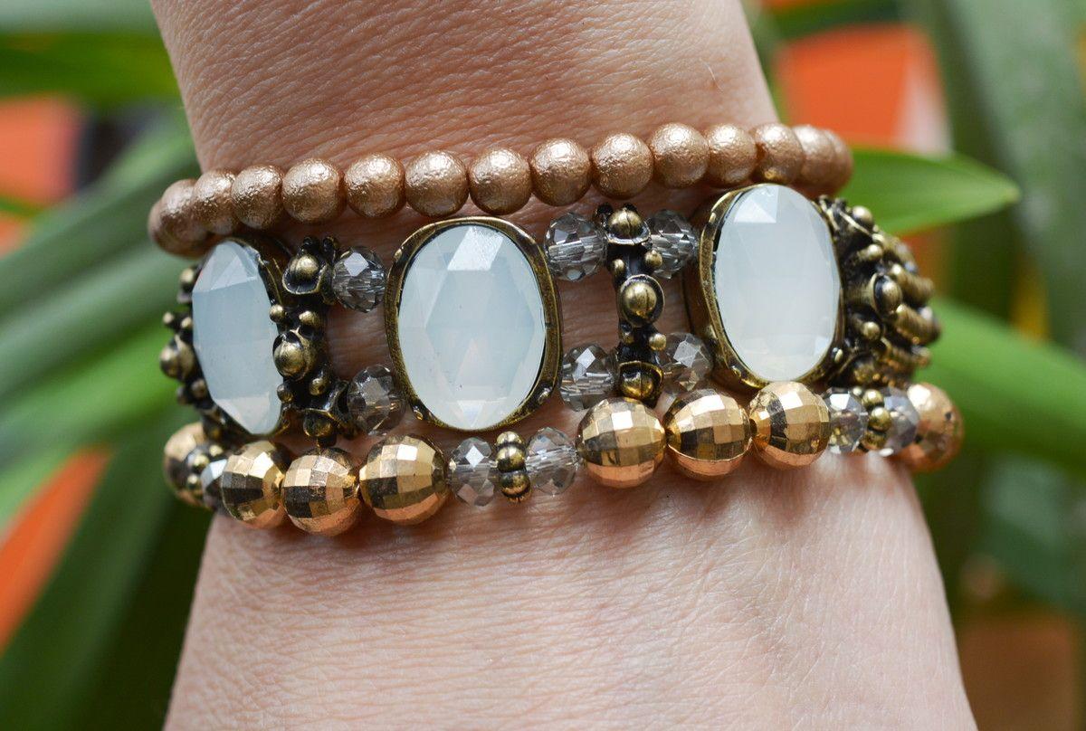 Mix de pulseiras com 3 pulseiras sendo 1 bracelete com pedraria branca, 1 contas metálicas pequenas e 1 com contas e cristais Brancos