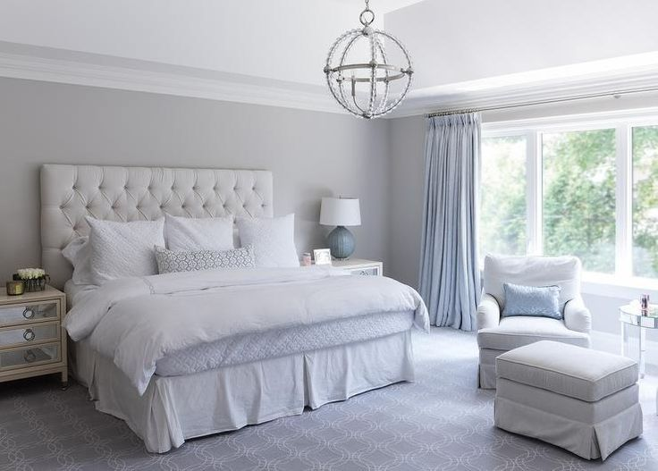 Blue and gray bedroom features a high ceiling accented with a Danville  Sphere Chandelier illuminating a white velvet tufted headboard on bed  dressed in ...