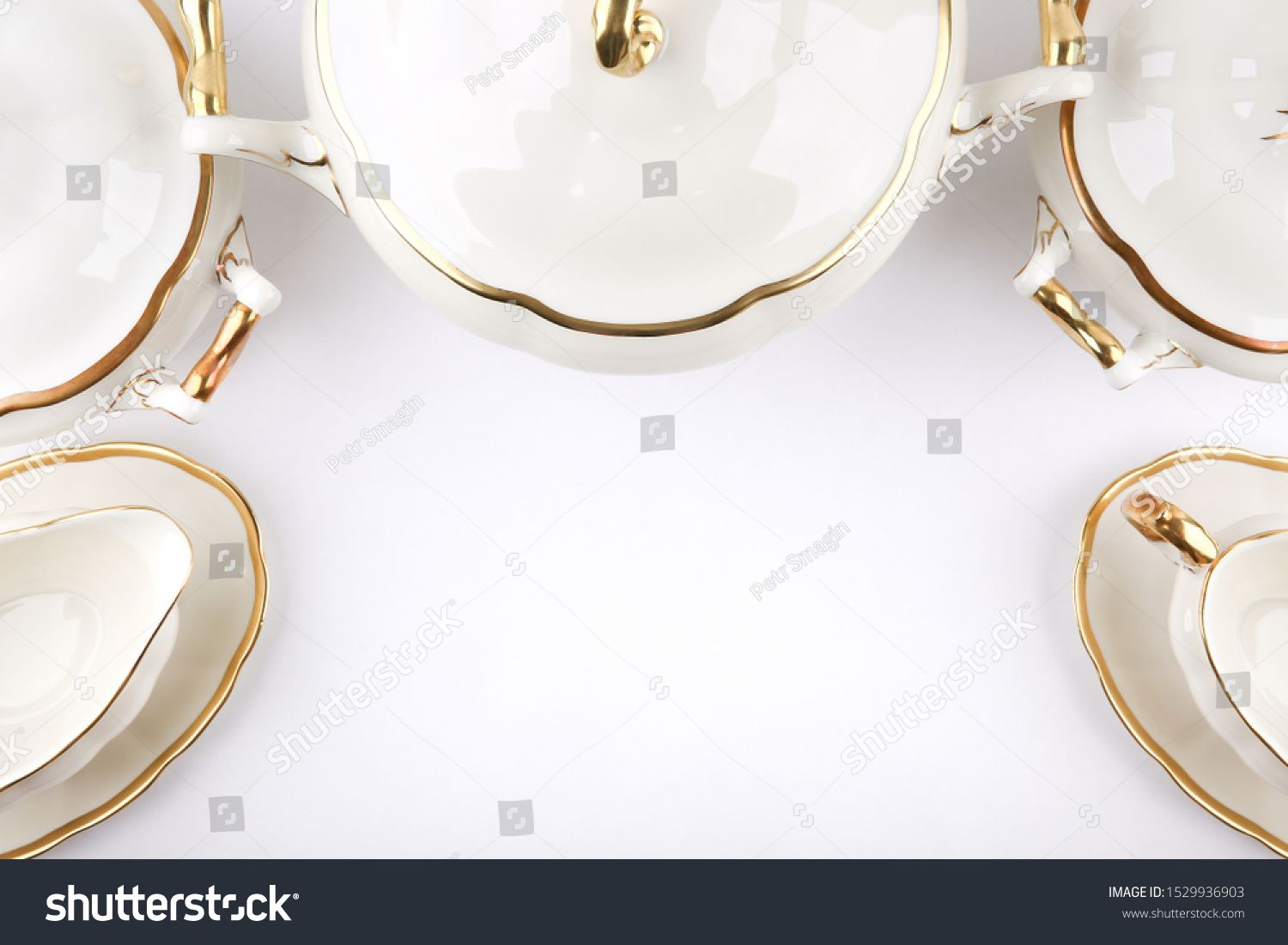 vintage ceramic tureens and gravy boats with gilding on a white background with copy space top view