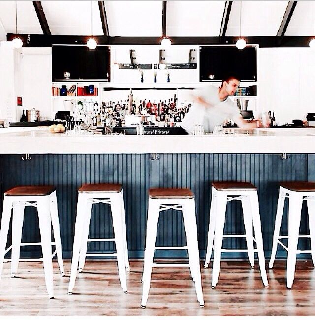 White stools against navy wood panelling