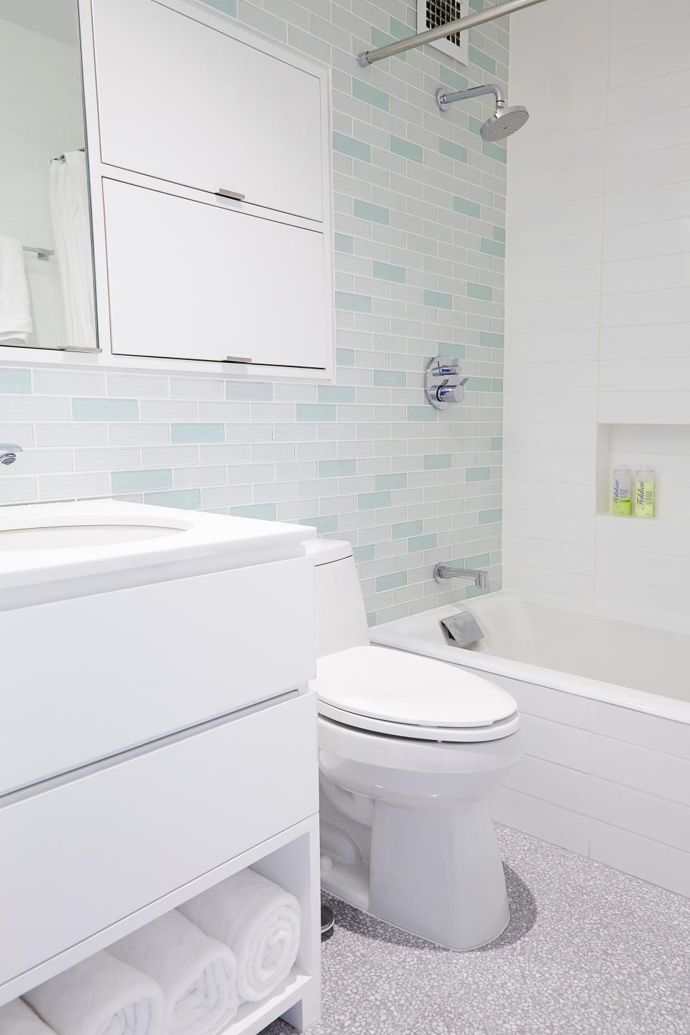 Walk in bathroom design with blue glass tiles walls and dark beige floors white countertop wooden cabinets undermount sink panel do  also