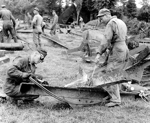 US Army engineers fabricating the hedge cutter tool, to be fitted to the Sherman tank from the steel beach obstacles left behind by the Germans. 9 July 1944.