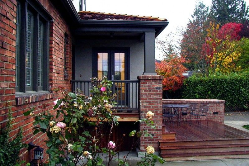 Brick House In Red Brown Color With Wooden Deck Dark Stained Auburn Beige Painted Wall Porch Table Sets Black Trim Br Exterior Lamp Cover Of Maximizing