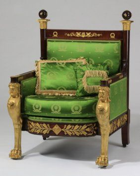 """French Empire Carved Bergere In Green Silk Late 19th or early 20th century French Empire style carved and parcel gilt bergere, with sphere capped finials flanking the straight crestrail adorned with gilt wreaths and scroll, with a laurel adorned skirt, the front legs in the form of term figures ending in large paw feet, upholstered in green silk with two matching throw pillows, 44.5""""h x 32.5""""w x 27""""d."""
