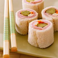 Kid Sushi:  2 slices Turkey;   2 strips Swiss Cheese; 2 slices Bread; 1 teaspoon ranch dressing; 1 tablespoon thinly shredded carrots; 2 sweet baby pickles    Method  Place two slices of white bread with the crusts cut off on a flat surface side-by-side. Using a rolling pin, or glass, gently flatten and fuse the bread slices together. Spread the ranch dressing over the inside middle of the flat bread slices. Place two slices of the ham on top of the ranch dressing. Place the shredded carrots…