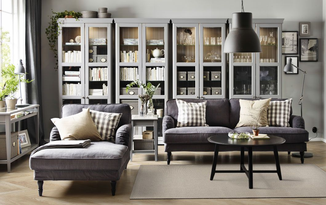 A living room with a grey three-seat sofa, chaise longue and a black