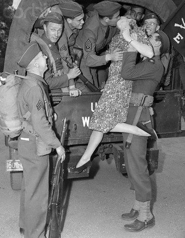 3/12/1941- Picture shows a woman (Martha O'Driscoll) Kissing a soldier good-bye before leaving for WWII. She is being held up by another soldier and kissing a boy through the back of a truck