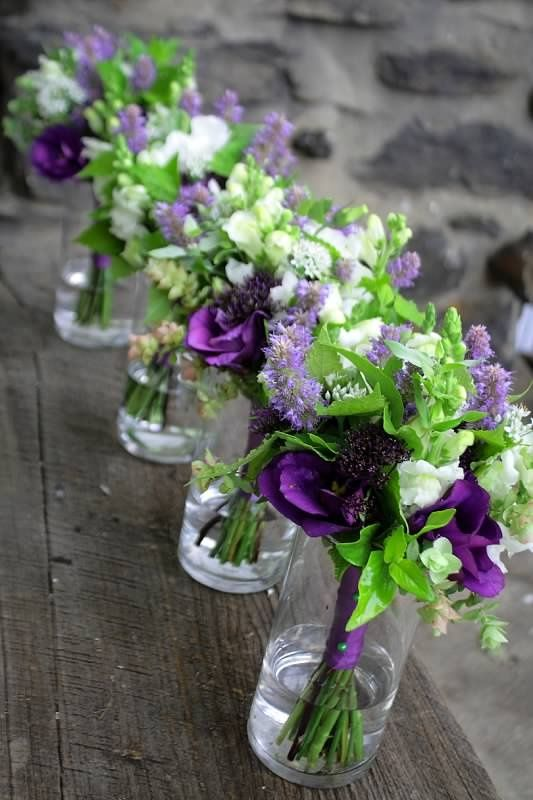 Wedding flowers green and purple but in mason jars instead