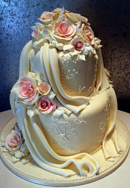Floral Rose With Drapery  Tiered cake with white chocolate roses and fondant drapery.