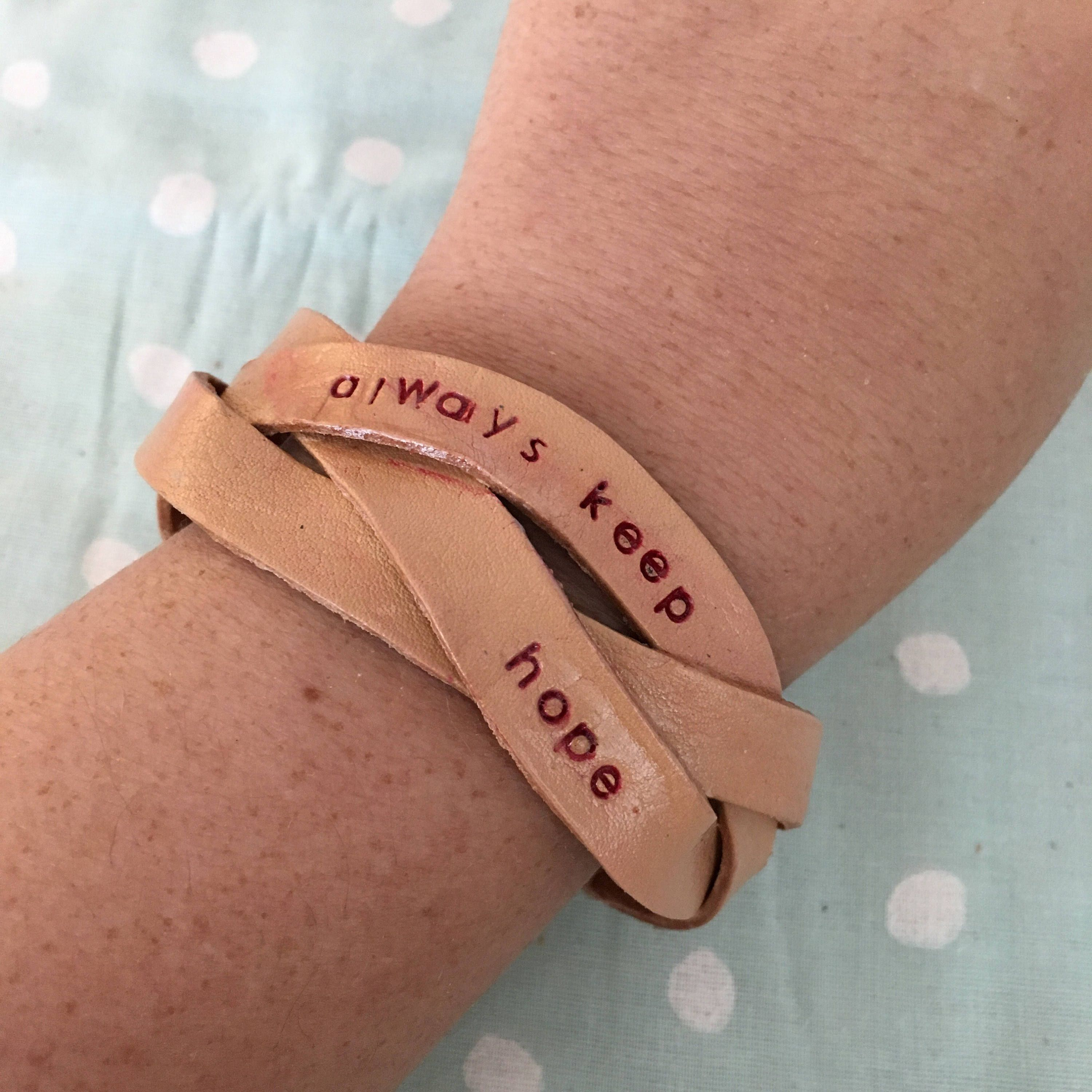 This unstained natural leather bracelet was hand stamped hand