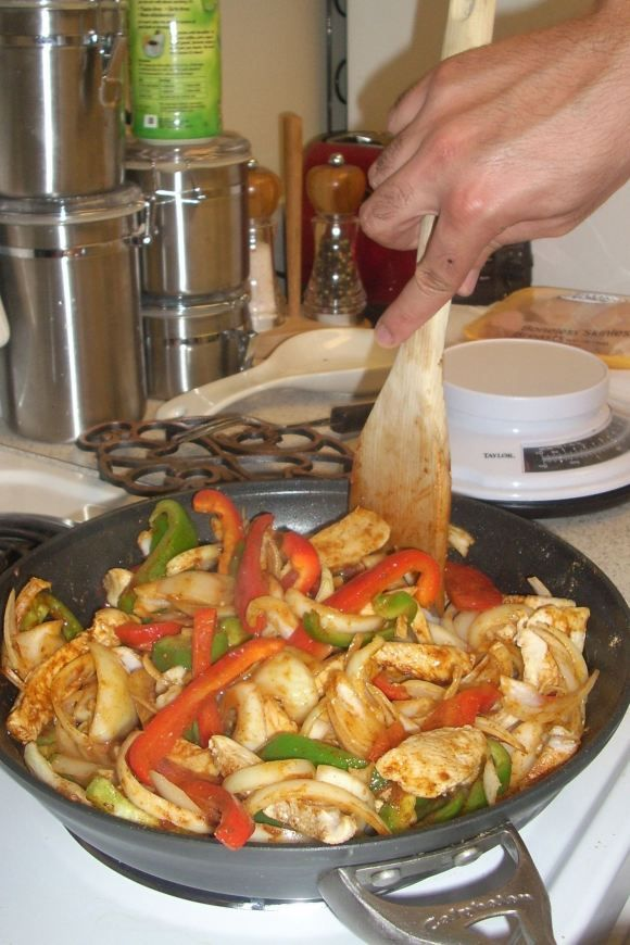 RUSH HOUR CHICKEN FAJITAS 2 medium green or red bell pepper, or combination 2 medium onions 2 garlic cloves, peeled 1 1/2 lbs boneless, skinless chicken breasts 1 pkg taco seasoning (or 2 tbsp Chipotle rub) 1 tbsp vegetable oil 1/4 cup water OPTIONAL: flour tortillas shredded cheddar cheese sour cream salsa
